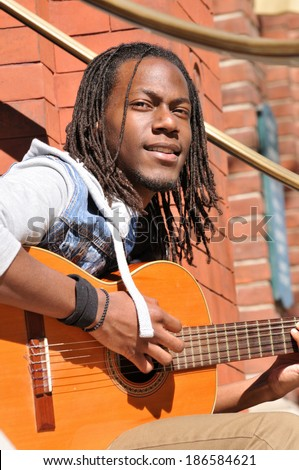 happy young African American man playing the guitar in the city - stock photo