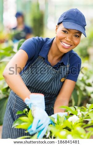 happy young african american nursery worker gardening - stock photo