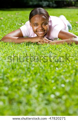 happy young african american woman lying on grass - stock photo