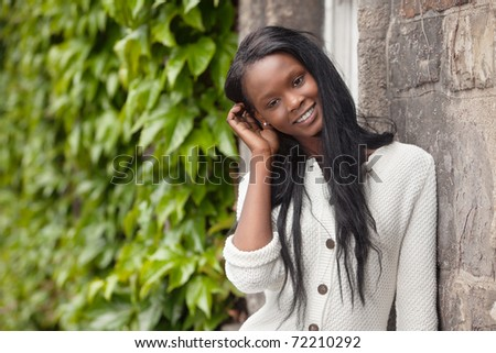 Happy young African American woman standing outdoors and smiling - stock photo