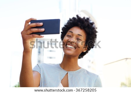 Happy young african american woman taking a selfie with her mobile phone - stock photo