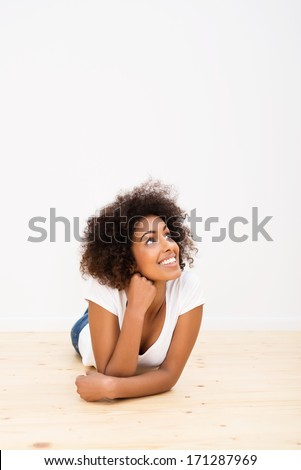 Happy young African American woman with a big frizzy afro hairstyle lying on the hardwood floor in her new house daydreaming with a white wall behind with copyspace - stock photo