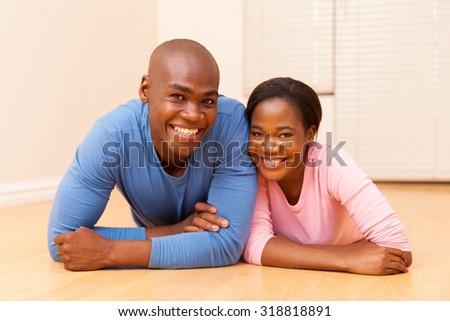 happy young african couple lying on the floor - stock photo