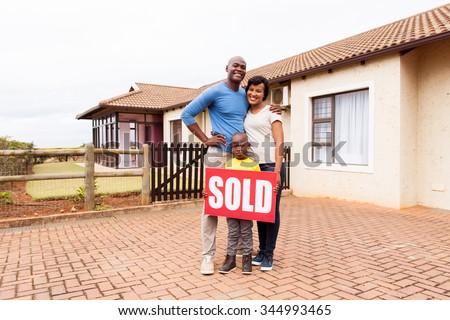 happy young african family in front of their home with sold real estate sign - stock photo
