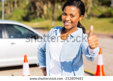happy young african girl standing in driving school giving thumb up - stock photo
