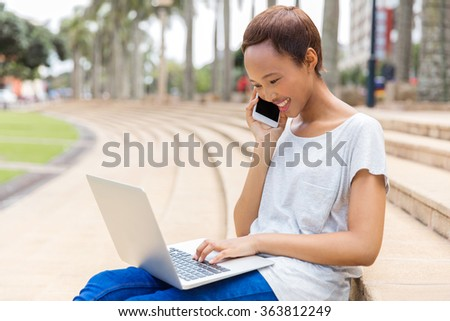 happy young african girl talking on mobile phone and using laptop - stock photo