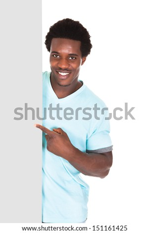Happy Young African Man In Casual Standing Behind The Placard Over White Background - stock photo