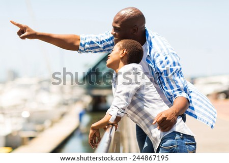 happy young african man pointing at the harbor with girlfriend - stock photo