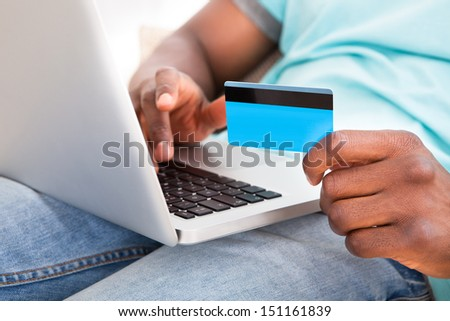 Happy Young African Man Using Laptop Sitting On Couch At Home - stock photo
