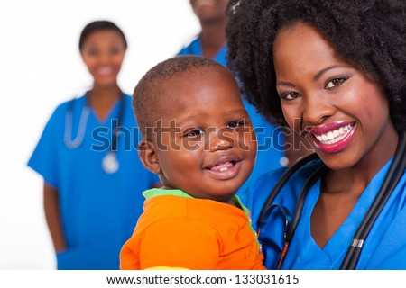 happy young african nurse carrying baby boy with colleagues on background