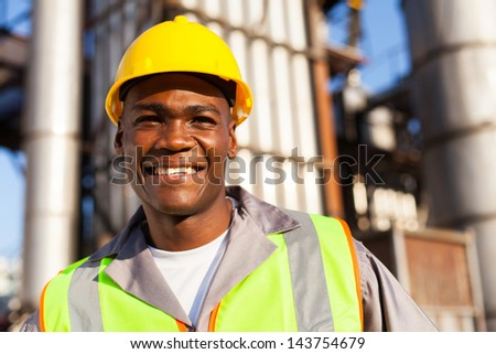 happy young african worker in petrochemical plant - stock photo