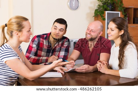 Happy young agent explaining to group of people the contract terms
