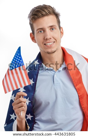 Happy young American patriot man celebrating 4th of July holiday with flag of United States in hand covered by big flag. Attractive model with toothy smile isolated on white