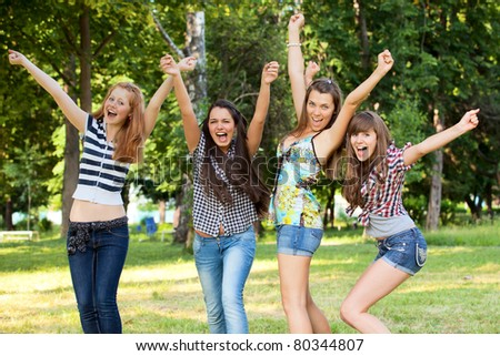 happy young and attractive girlfriends in park - stock photo