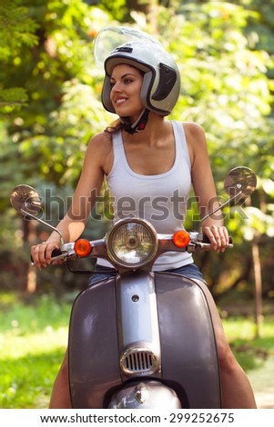 Happy young and beautiful woman on a scooter on the street and smiling - stock photo