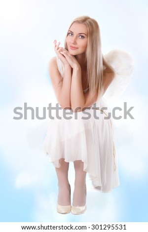 Happy young angel sitting on a cloud - stock photo