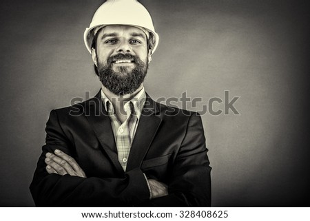 Happy young architect with hardhat and arms folded over gray background - stock photo