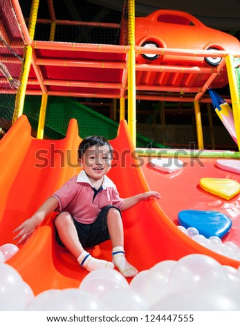 Happy young Asian boy playing in indoor playground
