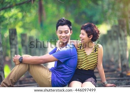 Happy young asian couple in love sitting on a park