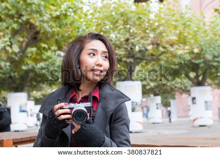 Happy Young Asian girl with camera walking outdoors, Asian girl In Europe travel.  - stock photo