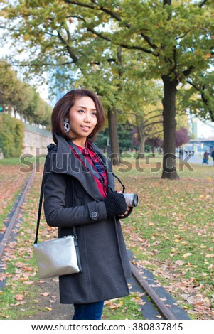 Happy Young Asian girl with camera walking outdoors, Asian girl In Europe travel.