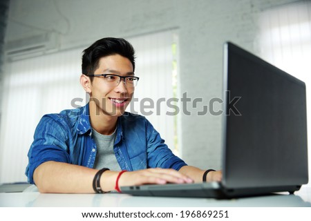 Happy young asian man working at office - stock photo