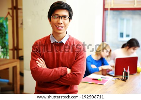 Happy young asian student in classroom - stock photo