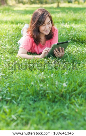 Happy Young Asian Woman Holding Digital Tablet and Smiling