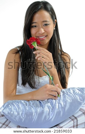 Happy young Asian woman holding red carnation in bed