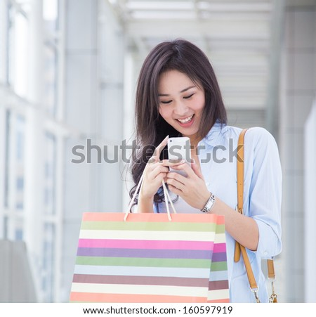 Happy young Asian woman taking photo using her mobile phone.