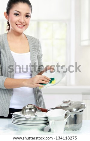 Happy Young asian Woman Washing Dishes in the kitchen - stock photo