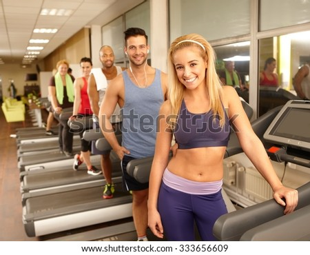 Happy young athletic people smiling in gym, standing in running machine. - stock photo