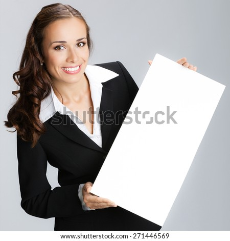 Happy young attractive businesswoman showing signboard with blank copyspace area for text or slogan - stock photo