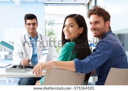Happy young attractive couple sitting at doctor's room on consultation. - stock photo