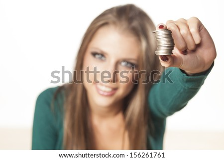 Happy young attractive girl is holding the coins in her hand - stock photo