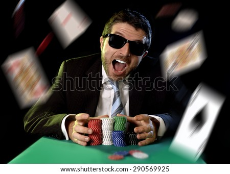 happy young attractive man grabbing poker chips after winning bet gambling on table with playing cards on green felt at Casino and chips and cards flying all around - stock photo