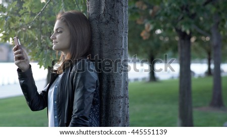happy young attractive women using smart phone device networking with social media app. female person outdoors at sunset