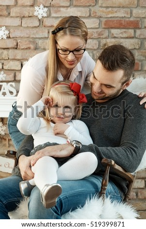 Happy young authentic family with little daughter at home.