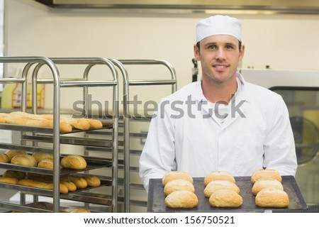 Happy young baker holding some rolls on a baking tray smiling at the camera - stock photo