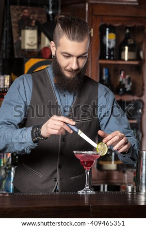 Happy young barman serving cocktail at the bar. - stock photo
