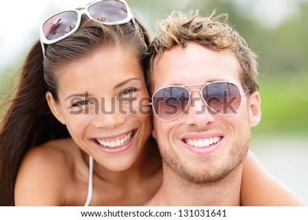 Happy young beach couple closeup portrait outdoors in sun. Young people wearing sunglasses eyewear. Joyful interracial couple, Asian woman, Caucasian man. - stock photo