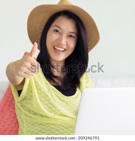 Happy young beautiful asian woman using laptop, Focus Select thumb. - stock photo