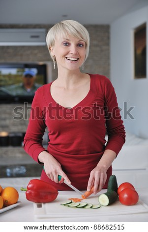 happy young  beautiful blonde  woman prepare food in  the kitchen at home