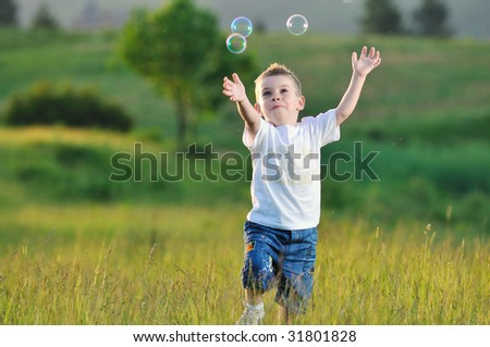 happy young beautiful child have fun on eadow with soap bubbles toy - stock photo