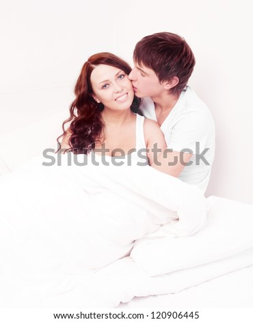 happy young beautiful couple in bed at home - stock photo