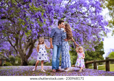 Happy Young beautiful family of mother, father and two little daughters in jacaranda blossom garden - stock photo