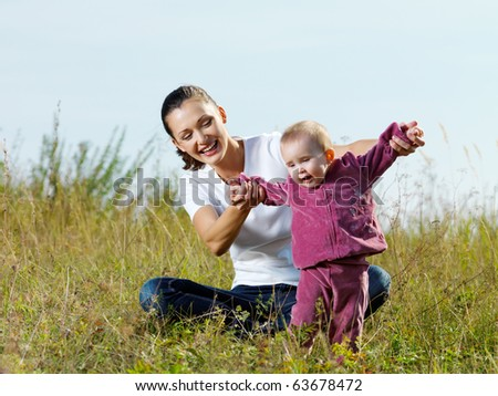 Happy young beautiful mather with smiling baby on nature outdoor - stock photo