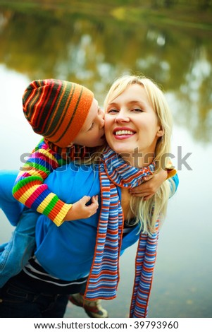 happy young beautiful mother giving her little son piggyback ride - stock photo