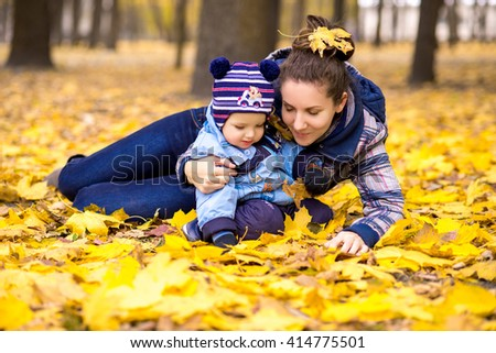 Happy young beautiful mother with her little son in the park  - stock photo