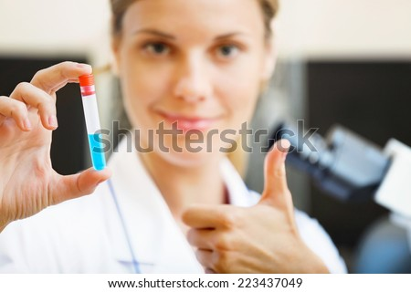 Happy young beautiful scientist holding samples with positive testing results in her hand. - stock photo